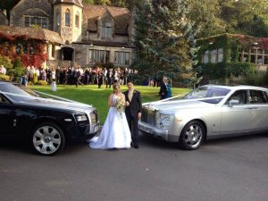 Wedding guests, bride and groom having photoshoot on grass next to two vintage classical cars