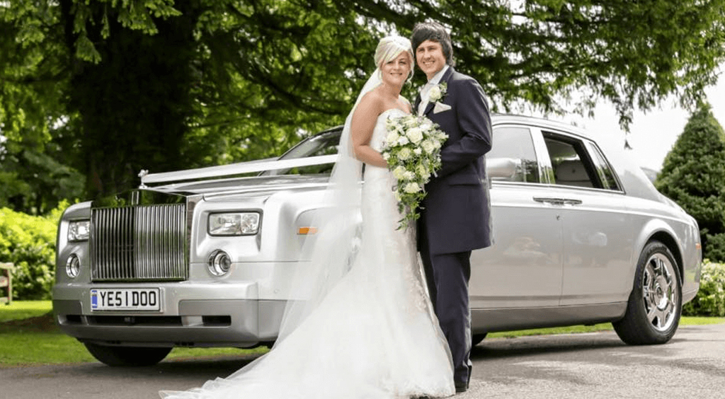 Happy couple having photoshoot next to Rolls Royce vintage car