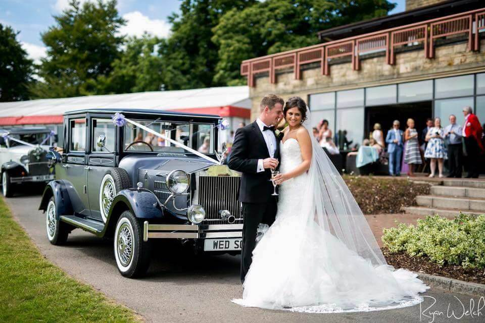 Happy couple celebrating wedding outside venue with viscount classic wedding car